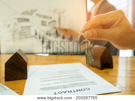Real estate trading concepts,Close-up House key in hand The back is a house sketch,Modell house and contract documents placed on the table.