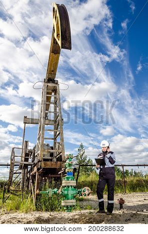 Woman engineer in the oilfield near pump jack wearing white helmet and work clothes. Industrial site background. Oil and gas concept.