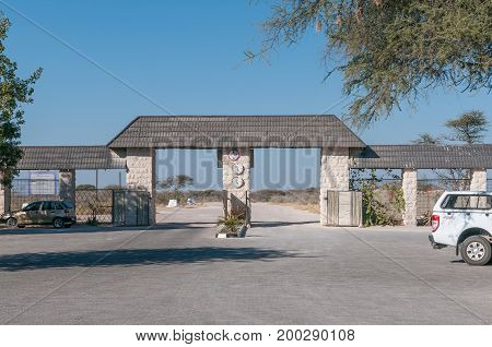 ETOSHA NATIONAL PARK NAMIBIA - JUNE 22 2017: The Eastern entrance to Okaukeujo Rest Camp in the Etosha National Park. The clocks indicate gate opening and closing times