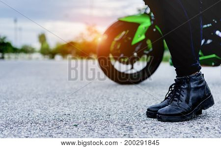 Young woman biker holding helmet equipment with jacket for safety protection when over high speed walking to motorcycle on street travel lifestyle.
