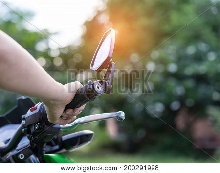 Closeup woman biker with glove safety ride acceleration speed control hand holing handbrake on motorcycle vehicle and nature background.