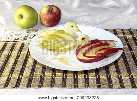 Food for children, duck carved out of apple on a plate closeup