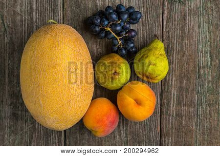 Melon, Grapes, Peach And Pear On Old Wooden Table.
