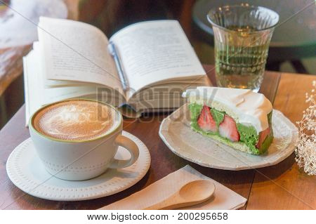 Top view of coffee cup and green tea cake  book on table in coffee shop relax time