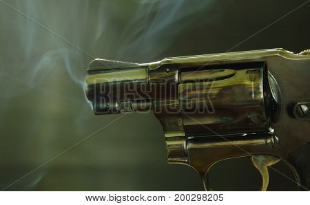 revolver gun with smoke floating in the air after shoot on black background