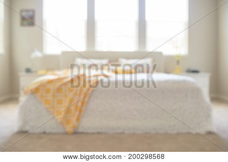 Blurred sunny bedroom in white and yellow colors, cozy and warm.