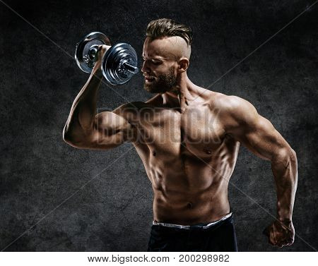 Athletic man doing exercises with dumbbells at biceps. Photo of strong male with naked torso on dark background. Strength and motivation.