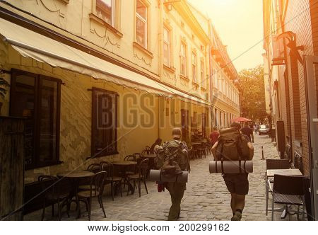 Tourists walking along a quiet street witch a lot of cafes