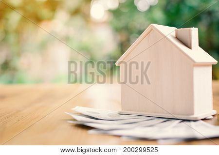 Wood house with dollar money on table tree bokeh background concept save money for home selective and soft focus vintage tone