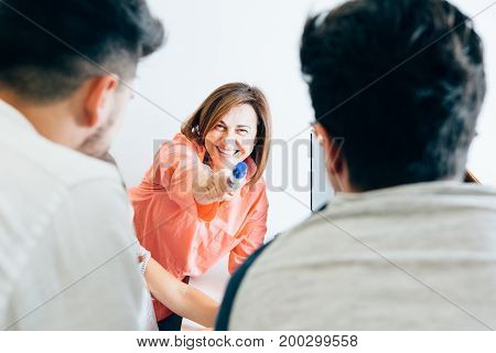 Cheerful woman pointing at students while working with them and studying new material.
