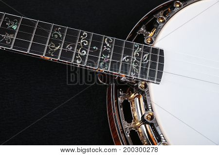 Banjo. Mahogany banjo luxury gold inlaid with mother of pearl on a black background.