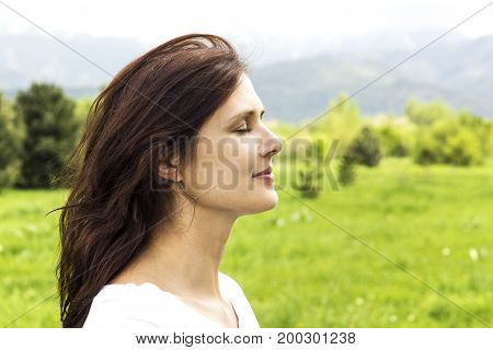 young woman with eyes closed breathing deeply fresh air in the mountains