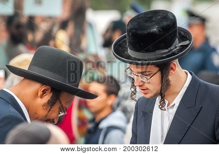 Uman Ukraine - 2 October 2016: Rosh Hashanah Jewish New Year 5777. It is celebrated at the grave of Rabbi Nachman. Pilgrims in traditional festive clothes. Conversation between two Hasidic Jews.
