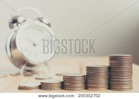 Stack of coins placed on stairs on wooden board with clock Finance and investment have increased in value over time concept