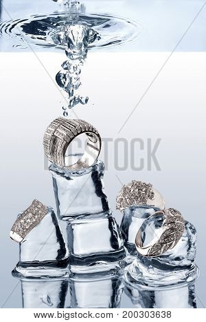 Creative photo of jewelery being dropped on ice cubes underwater