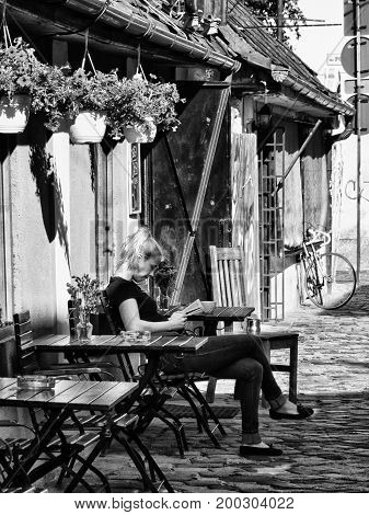 CLUJ-NAPOCA ROMANIA - AUGUST 27 2015: Young girl reading the paper at an outdoor street cafe table annexed to an old building on a cobblestone street - B&W