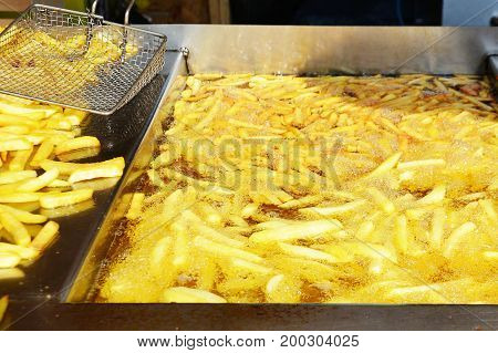 Tasty French fries boiling in hot oil