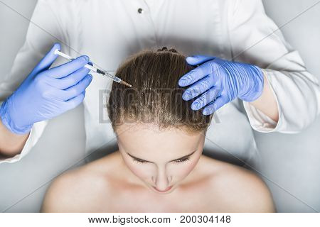 Doctor aesthetician with blue medical gloves and white medical gown makes rejuvenation beauty injections in the head of female patient for hair growth and to prevent boldness.