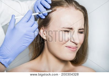 Doctor aesthetician with blue medical gloves makes painful hyaluronic acid rejuvenation beauty injections in the head of female patient for hair growth and to prevent boldness.