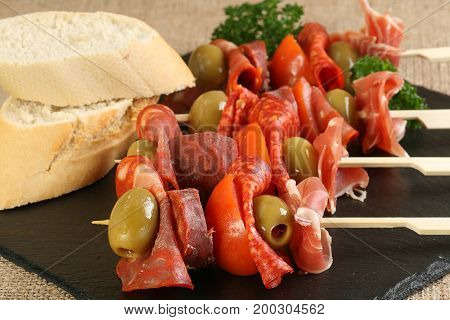 tapas meat selection with olives and tomatos on skewers
