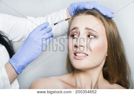 Doctor aesthetician with blue medical gloves and syringe trying to make hyaluronic acid rejuvenation beauty injections in the head or face of frightened female patient.
