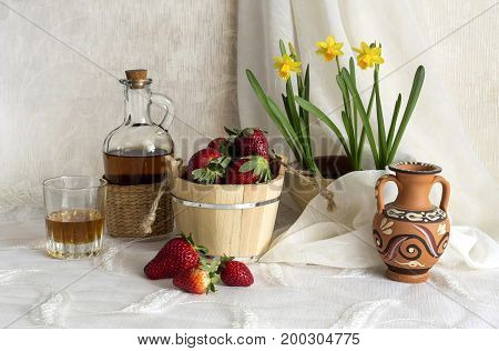 Still life with strawberries, brandy and daffodils on a table close-up