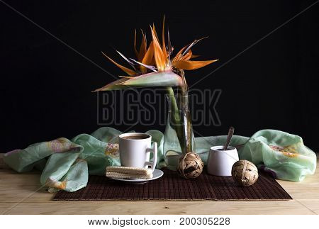 Still life with strelitzia and a cup of coffee on a table close-up