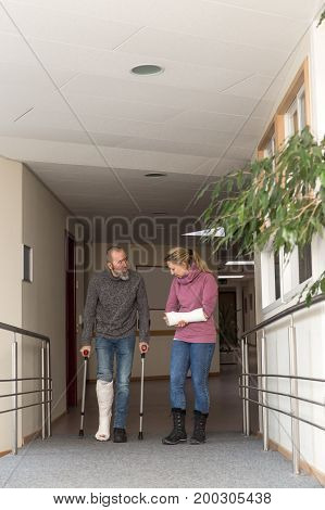 two persons with cast on on leg and arm male is walking with crutches
