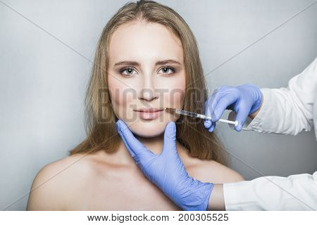 Doctor aesthetician in blue medical gloves makes hyaluronic acid beauty injections in lips to make correction and augmentation of the lips of female patient