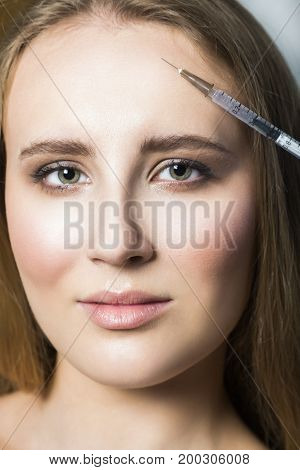 Doctor aesthetician makes hyaluronic acid beauty injections in the forehead of blond young female patient