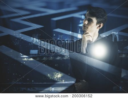 Thoughtful young businessman on abstract city background with maze labyrinth. Freedom concept. Double exposure