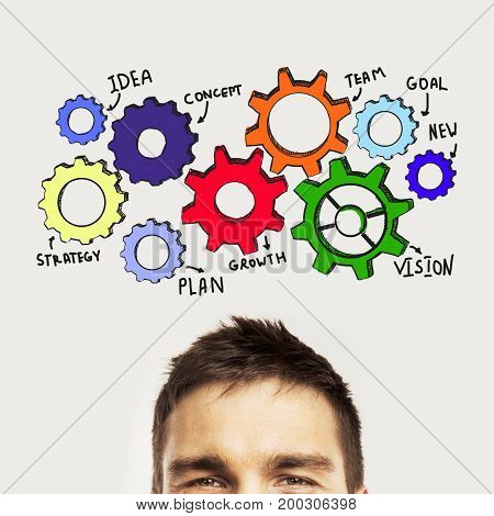 Portrait of attractive young man on light gray background with colorful cogwheels. Engineering concept