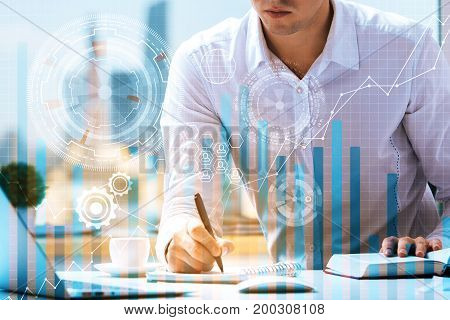Young businessman doing paperwork at office workplace with laptop coffee cup and creative business hologram. Acocunting concept. Double exposure