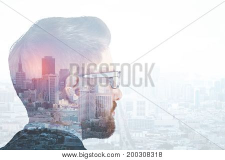 Headshot of thoughtful young businessman looking at city with copy space. Employment concept. Double exposure