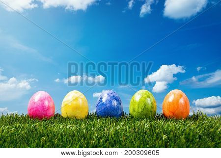 A row of five colorful easter eggs on green grass in Springtime.