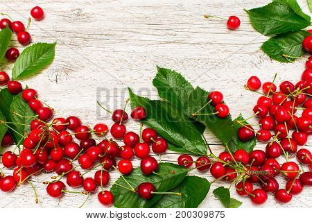 White wooden background with scattered ripe red cherries with green leaves close-up