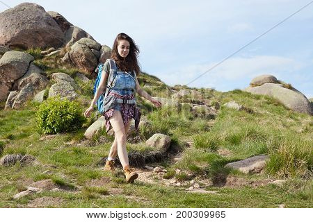 Woman hiker smiling and walking with hiking poles.
