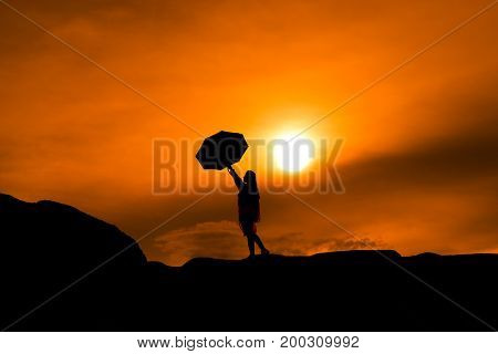 Young girl asian stand with raincoat and umbrella on mountain in the after rainy season and sunset silhouette