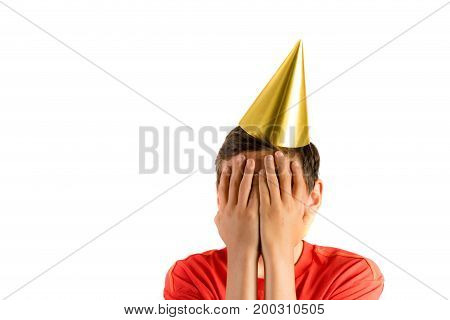 Young teenage boy isolated on white covering his eyes at a party