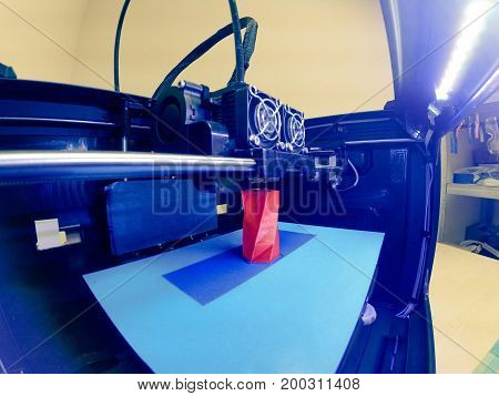 3D printer prints the form of molten plastic red close-up. Automatic three dimensional 3d printer performs plastic modeling in laboratory. Progressive modern additive technology