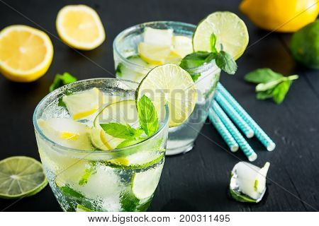 Cold and refreshing infused detox water with lime with lemon in a glass