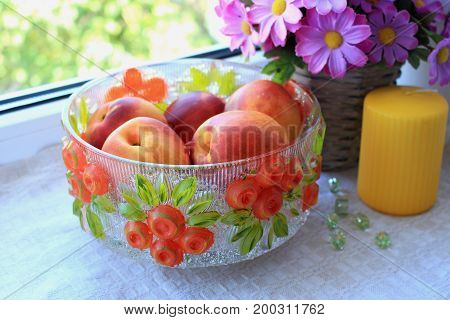 Composition with nectarines in glass bowl candle and artificial flowers on window sill on light background