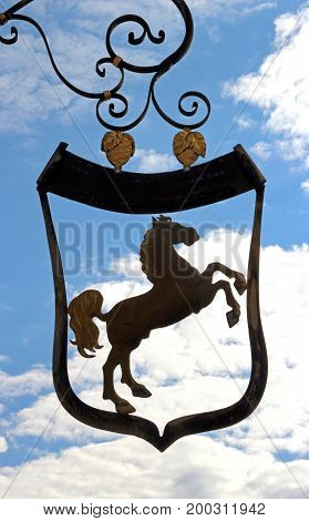 old inn sign with a horse in front of blue and white sky shield