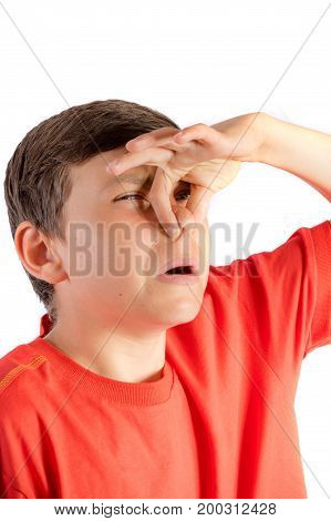 Young teenage boy isolated on a white background holding his nose