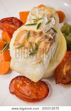 grilled cod with mashed potato carrots slice tomato and mushy pea