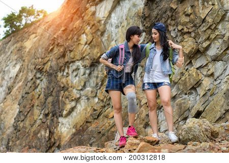 Young girl asian with backpack help friend hurt leg first aid elementary on the mountain travel trip adventure
