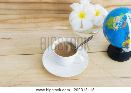 A mug of coffee in white cup placed on wood.