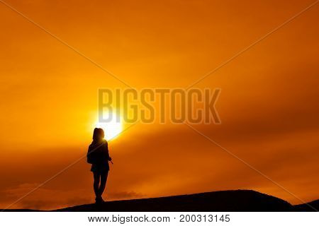 Young girl asian with backpack travel trip stand finish destinations on the mountain looking view sunset silhouette