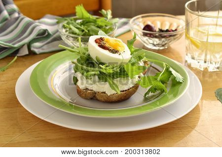 Toast with cream cheese arugula and boiled egg healthy breakfast