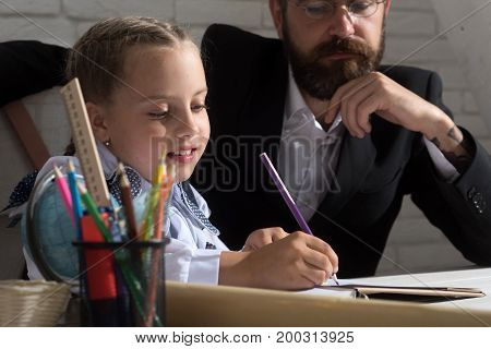 Family Sits By Desk With School Supplies. Classroom And Education